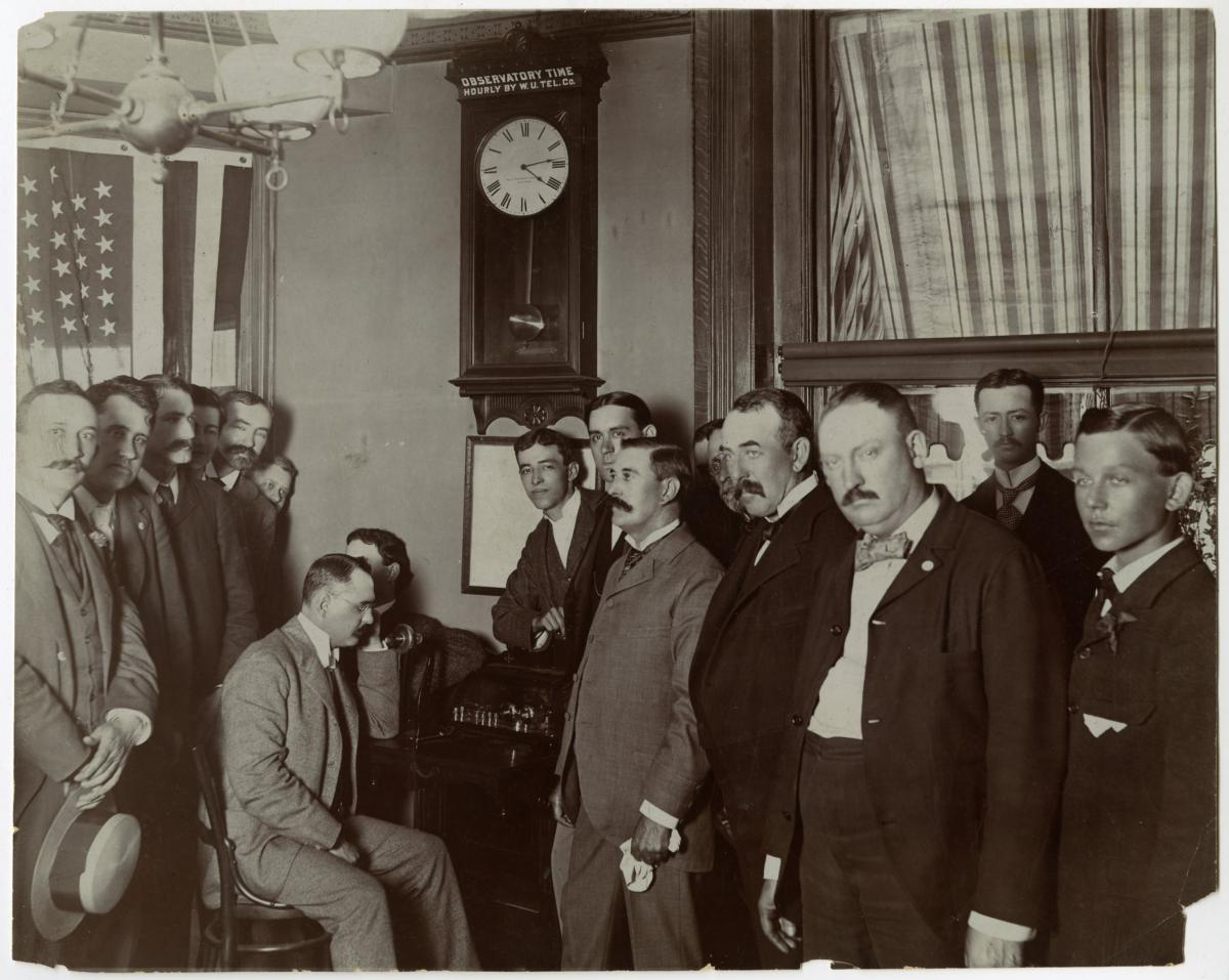 Interior group scene. Sign above clock reads Observatory Time Hourly by W. U. Tel. Co.